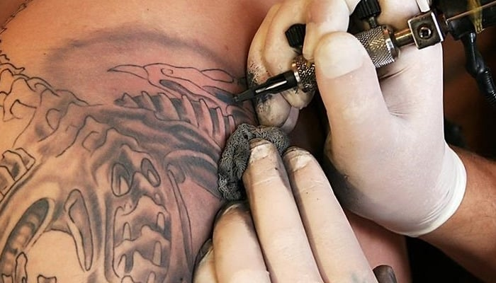 Persona tatuando
